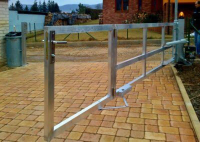 Brána jednokřídlá průmyslová hliníková s elektrickým pohonem s výstražným majákem a s brankou