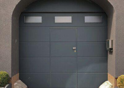 """sekční garážová vrata Hörmann LPU, drážka """"L"""" s integrovanými dveřmi, prosklenou lamelou a předsazenou blendou v antracitové barvě."""