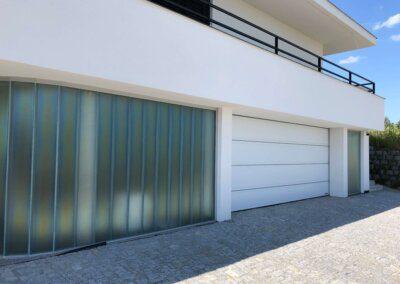 """Sekční bílá garážová vrata Hörmann LPU, drážka """"T"""" s ozdobným vodorovným nerezovým pruhem, hladký povrch SilkGrain na moderní vile. Jednoduché a elegantní řešení vrat do garáže."""